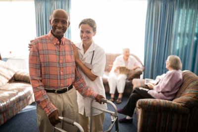 man smiling with crutches together with healthcare worker